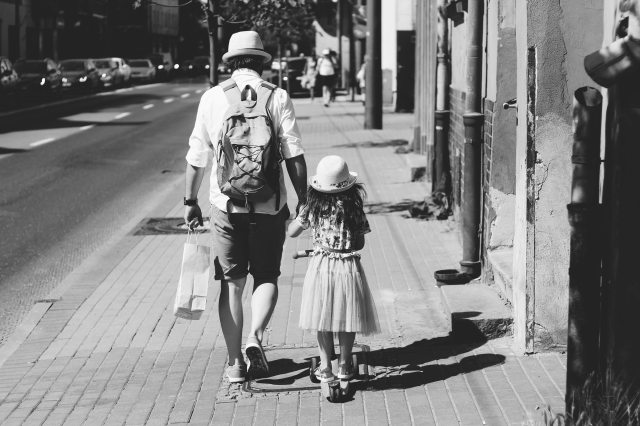 man-holding-girl-while-walking-on-street-1194209