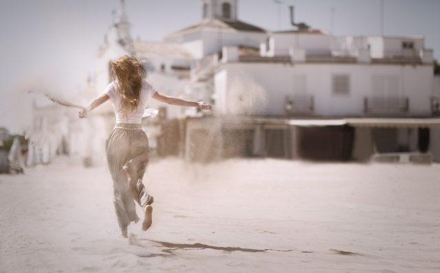 woman-running-on-sand-near-white-concrete-building-736505.jpg