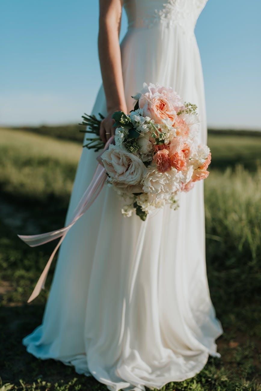 woman wearing white wedding dress holding flower bouquet standing on green field